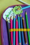 Farbige Bleistifte in einem Bleistiftkasten und in einer Kind-` s Zeichnung Lizenzfreies Stockbild