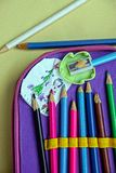 Farbige Bleistifte in einem Bleistiftkasten und in einer Kind-` s Zeichnung Lizenzfreie Stockfotografie