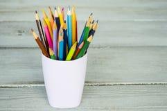 Farbige Bleistifte in einem Glas auf einem hölzernen Hintergrund Stockfoto
