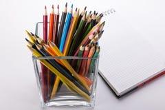 Farbige Bleistifte in einem Glas und in einem Notizbuch auf einem weißen Hintergrund stockfoto
