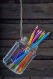 Farbige Bleistifte in einem Glasglas Hintergrund Stockbild