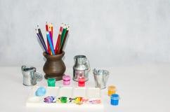 Farbige Bleistifte in einem keramischen Vase, in einer Palette und in den Farben Stockfotografie