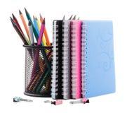Farbige Bleistifte in einer Schale, in einigen Notizbüchern und in einigen Klammern für Papiere Das Konzept der Bildung Lizenzfreie Stockfotografie