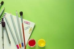 Farbige Bleistifte, Farben, Kompassse, Büroklammern und Bürsten auf einem Notizbuch, grüner Hintergrund mit Kopienraum Stockfoto