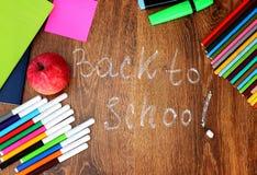 Farbige Bleistifte, Filzstifte und Markierungen, Notizbücher, Aufkleber ein roter Apfel auf dem hölzernen Hintergrund mit zurück  Lizenzfreies Stockbild