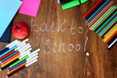 Farbige Bleistifte, Filzstifte und Markierungen, Notizbücher, Aufkleber ein roter Apfel auf dem hölzernen Hintergrund mit zurück  Stockbild