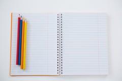 Farbige Bleistifte gehalten auf dem Buch Lizenzfreies Stockfoto
