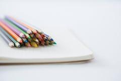 Farbige Bleistifte gehalten auf dem Buch Lizenzfreie Stockfotografie