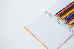 Farbige Bleistifte gehalten auf dem Buch Stockfotografie