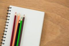 Farbige Bleistifte gehalten auf dem Buch Stockbild