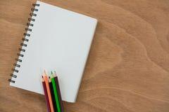 Farbige Bleistifte gehalten auf dem Buch Lizenzfreies Stockbild