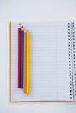 Farbige Bleistifte gehalten auf dem Buch Stockfoto
