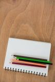 Farbige Bleistifte gehalten auf dem Buch Lizenzfreie Stockfotos