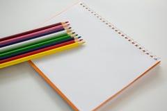 Farbige Bleistifte gehalten auf dem gewundenen Buch Stockfotografie