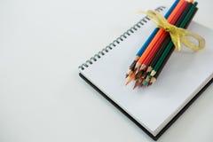Farbige Bleistifte gehalten auf dem gewundenen Buch Lizenzfreie Stockbilder
