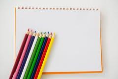 Farbige Bleistifte gehalten auf dem gewundenen Buch Stockfoto