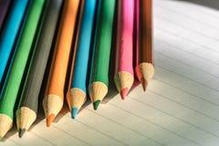 Farbige Bleistifte gesehen auf dem Schreibpapier, gesehen innerhalb eines Klassenzimmers Stockfotos