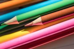 Farbige Bleistifte gesehen auf dem Schreibpapier, gesehen innerhalb eines Klassenzimmers Stockfoto