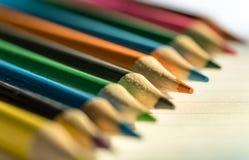 Farbige Bleistifte gesehen auf dem Schreibpapier, gesehen innerhalb eines Klassenzimmers Stockbilder