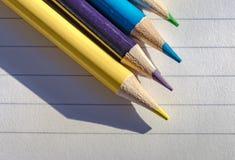 Farbige Bleistifte gesehen auf dem Schreibpapier, gesehen innerhalb eines Klassenzimmers lizenzfreie stockfotografie