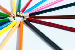 Farbige Bleistifte gestapelt in einem Kreis innerhalb der Stifte Stockfoto