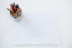Farbige Bleistifte hielten im Bleistifthalter, der auf leerem Papier gehalten wurde Lizenzfreie Stockbilder