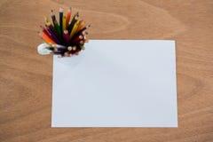Farbige Bleistifte hielten im Bleistifthalter, der auf leerem Papier gehalten wurde Stockfotografie