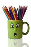 Farbige Bleistifte im grünen Becher mit Gesicht Lizenzfreie Stockfotografie
