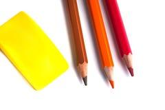 Farbige Bleistifte im Korb, im Radiergummi und im Bleistiftspitzer auf wh Lizenzfreie Stockbilder