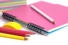 Farbige Bleistifte im Korb, im Radiergummi und im Notizbuch auf Weißrückseite Stockfotos