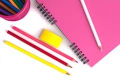 Farbige Bleistifte im Korb, im Radiergummi und im Notizbuch auf Weißrückseite Lizenzfreie Stockfotos