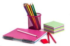 Farbige Bleistifte im Korb, im Radiergummi und im Notizbuch auf Weißrückseite Stockfotografie