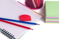 Farbige Bleistifte im Korb, im Radiergummi und im Notizbuch auf Weißrückseite Stockbilder