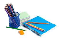 Farbige Bleistifte im Korb, im Radiergummi und im Notizbuch auf Weißrückseite Stockfoto