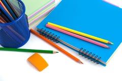 Farbige Bleistifte im Korb, im Radiergummi und im Notizbuch auf Weißrückseite Lizenzfreies Stockbild