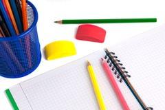 Farbige Bleistifte im Korb, im Radiergummi und im Notizbuch auf Weißrückseite Stockbild