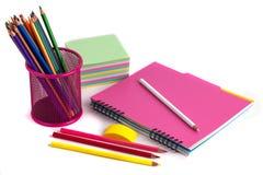 Farbige Bleistifte im Korb, im Radiergummi und im Notizbuch auf Weißrückseite Lizenzfreie Stockfotografie