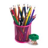 Farbige Bleistifte im Korb und im Bleistiftspitzer auf Weißrückseite Stockfotos