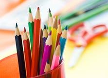 Farbige Bleistifte im roten Glas Stockbild