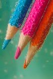 Farbige Bleistifte im Wasser mit Blasen Stockfotos