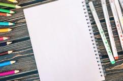 Farbige Bleistifte, Markierungen und Notizblock auf hölzernem Hintergrund Lizenzfreie Stockfotografie