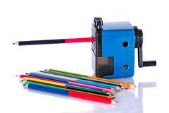 Farbige Bleistifte mit Bleistiftspitzer Lizenzfreie Stockfotos