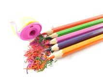 Farbige Bleistifte mit Bleistiftspitzer und Staub Lizenzfreie Stockbilder