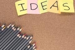 Farbige Bleistifte mit den Ideen geschrieben auf Post-Itanmerkungen Lizenzfreie Stockbilder