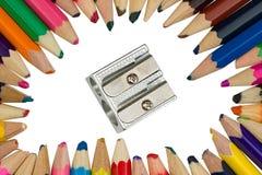 Farbige Bleistifte mit einem Bleistiftspitzer in der Mitte Lizenzfreies Stockfoto