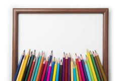 Farbige Bleistifte mit einem leeren Rahmen Stockbild