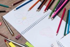 Farbige Bleistifte mit einem Notizbuch Lizenzfreies Stockfoto