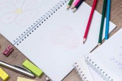 Farbige Bleistifte mit einem Notizbuch Lizenzfreies Stockbild
