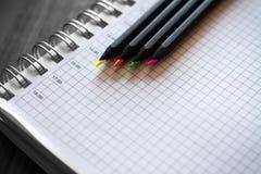 Farbige Bleistifte mit einem Notizbuch Stockfotos