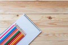Farbige Bleistifte mit einem Notizbuch auf dem Tisch Stockbild